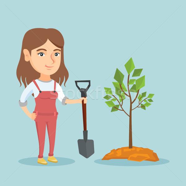 Young caucasian woman planting a tree. Stock photo © RAStudio