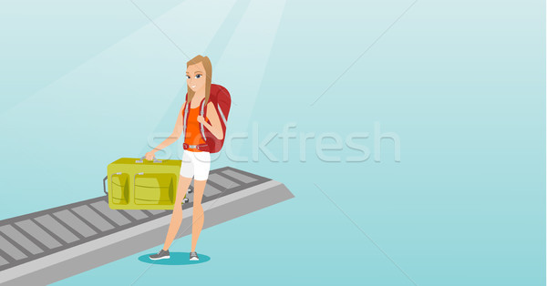Woman picking up suitcase from conveyor belt. Stock photo © RAStudio