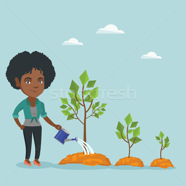 Young african business woman watering trees. Stock photo © RAStudio