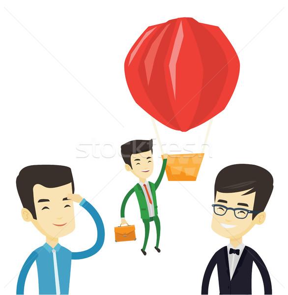 Business man hanging on balloon. Stock photo © RAStudio