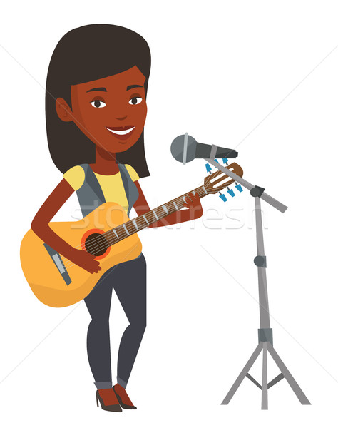 Woman singing in microphone and playing guitar. Stock photo © RAStudio