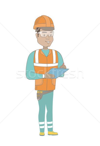 Young hispanic building inspector with clipboard. Stock photo © RAStudio