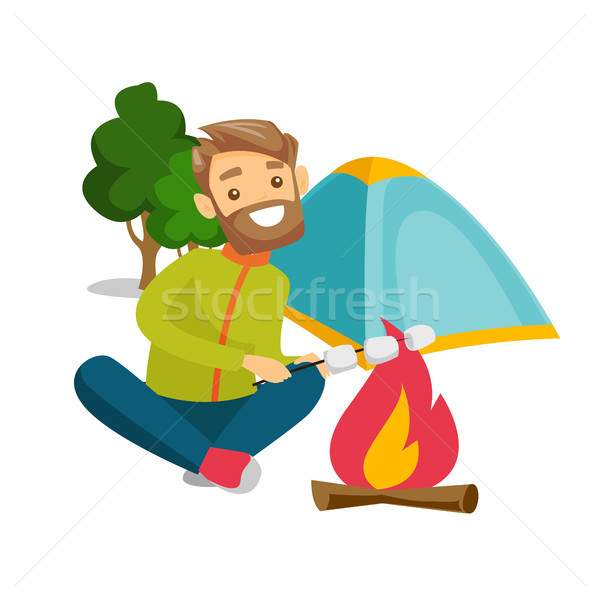 Caucasian man roasting marshmallow over campfire. Stock photo © RAStudio