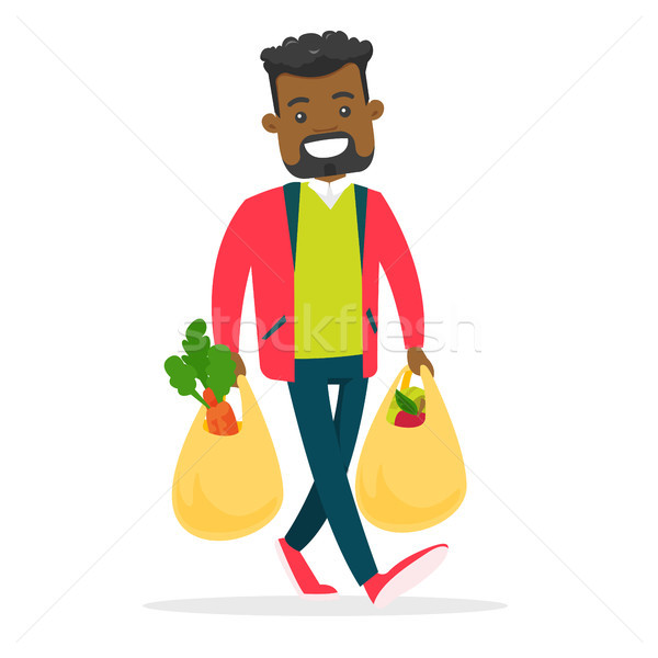 Young man holding shopping bags with groceries. Stock photo © RAStudio