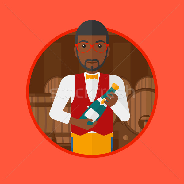 Waiter holding bottle in wine cellar. Stock photo © RAStudio