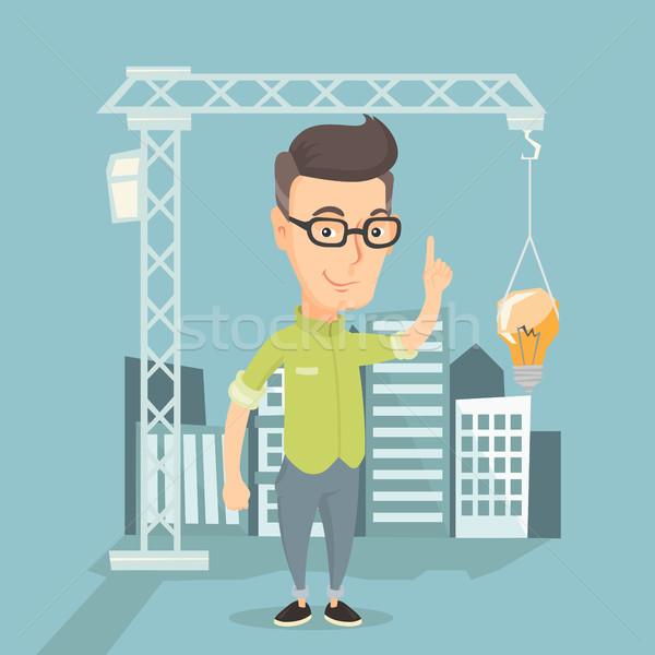 Man pointing at idea bulb hanging on crane. Stock photo © RAStudio