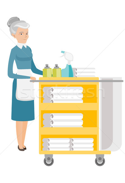 Senior chambermaid pushing cart with bed clothes. Stock photo © RAStudio