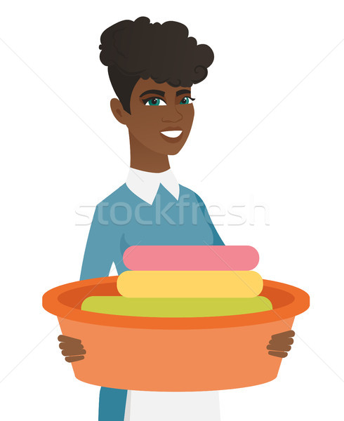 African housewife holding basin with dirty linen. Stock photo © RAStudio