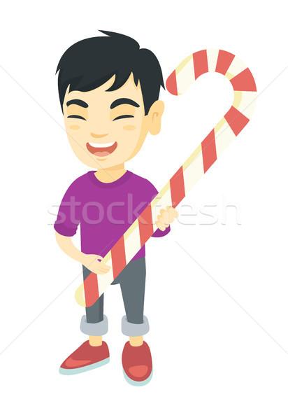 Asian little boy holding christmas candy cane. Stock photo © RAStudio