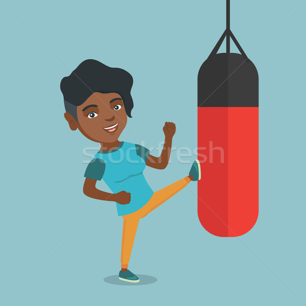 Young african woman exercising with punching bag Stock photo © RAStudio