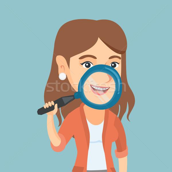 Woman examining her teeth with a magnifier. Stock photo © RAStudio