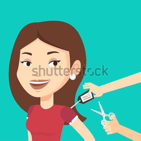 Woman cutting price tag off new t-shirt. Stock photo © RAStudio