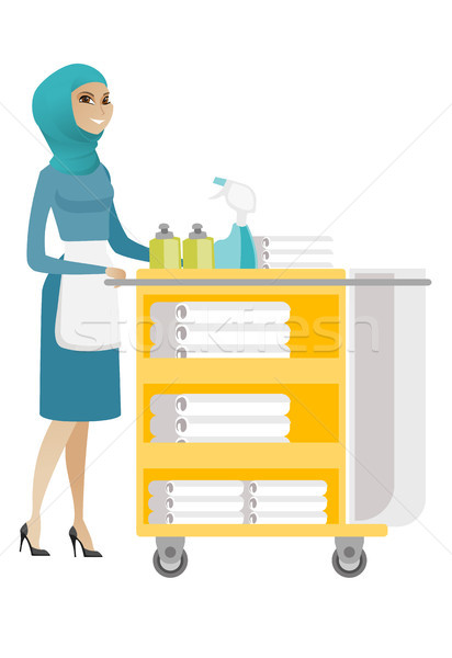 Muslim chambermaid pushing cart with bed clothes. Stock photo © RAStudio