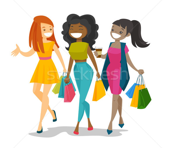 Young happy multicultural women shopping together. Stock photo © RAStudio