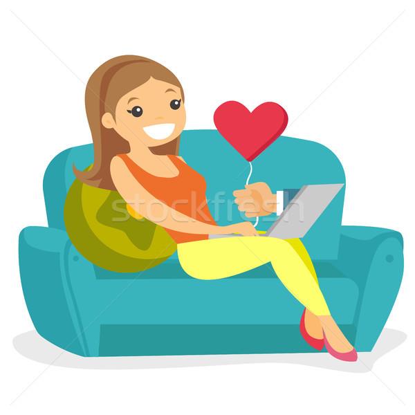 Genç kadın kalma çevrimiçi dizüstü bilgisayar kullanıyorsanız kadın kafkas Stok fotoğraf © RAStudio