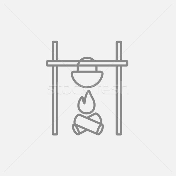 Cooking in cauldron on campfire line icon. Stock photo © RAStudio