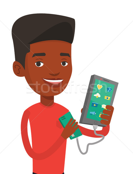 Stock photo: Man reharging smartphone from portable battery.