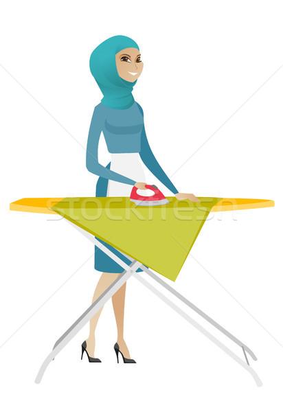Muslim maid ironing clothes on ironing board. Stock photo © RAStudio