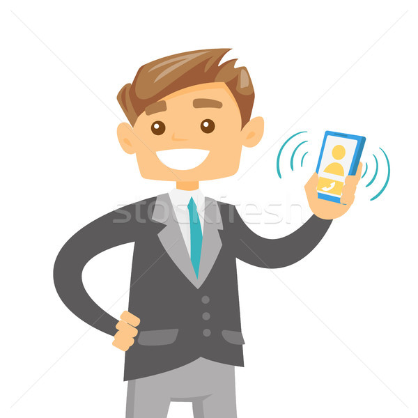 Young caucasian man holding ringing mobile phone. Stock photo © RAStudio