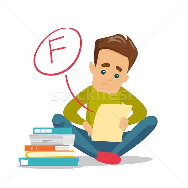 Sad student looking at test paper with bad grade. Stock photo © RAStudio
