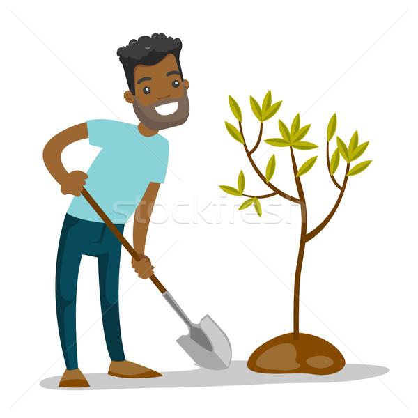 Young african-american gardener plants a tree. Stock photo © RAStudio