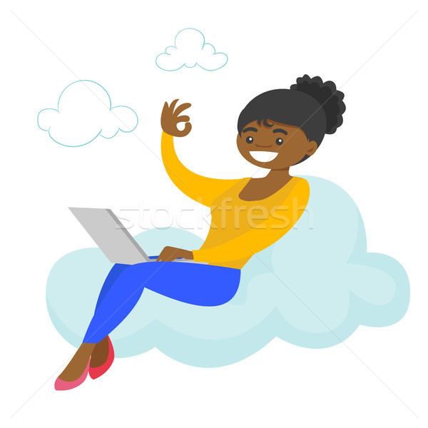 A woman on a cloud working on a laptop and showing ok sign. Stock photo © RAStudio