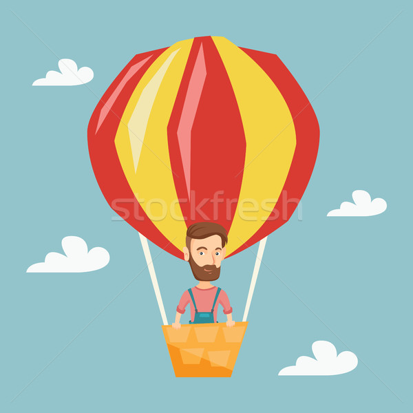 Young man flying in hot air balloon. Stock photo © RAStudio
