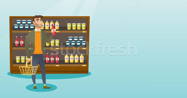Férfi tart bevásárlókosár üveg mártás fiatal Stock fotó © RAStudio