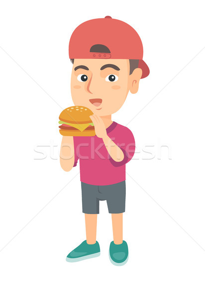 Little caucasian boy eating a hamburger. Stock photo © RAStudio
