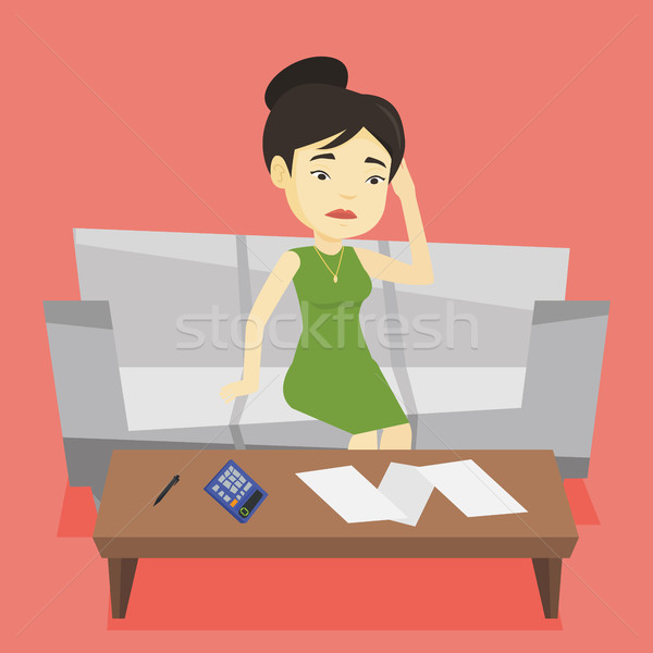 Unhappy asian woman accounting home bills. Stock photo © RAStudio