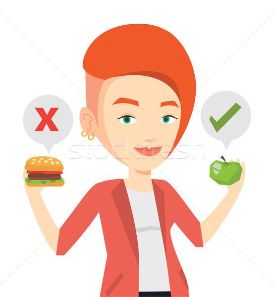 Woman choosing between hamburger and cupcake. Stock photo © RAStudio