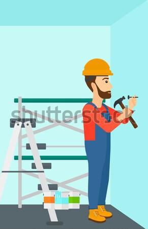 Constructor hammering nail. Stock photo © RAStudio