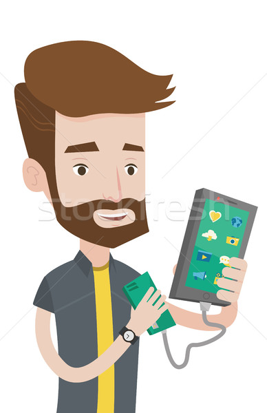 Man reharging smartphone from portable battery. Stock photo © RAStudio