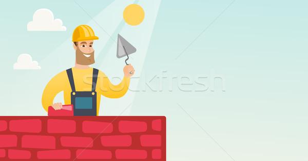 Murarz pracy cegły młodych uniform Zdjęcia stock © RAStudio