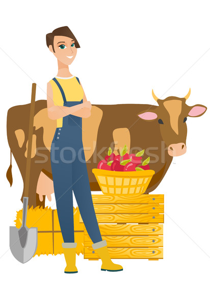 Farmer standing with crossed arms near cow. Stock photo © RAStudio