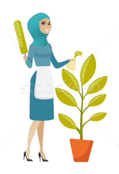 Young muslim housemaid watering flower with spray. Stock photo © RAStudio