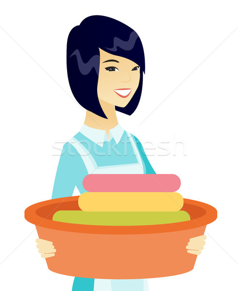 Asian housewife holding basin with dirty linen. Stock photo © RAStudio