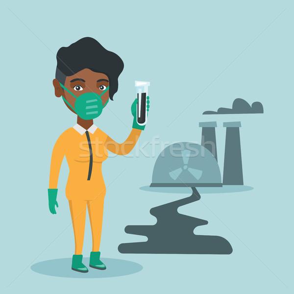 Scientist in yellow protective suit with test tube Stock photo © RAStudio