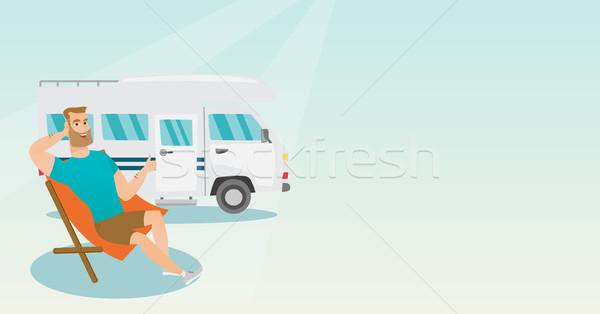 Man sitting in a chair in front of camper van. Stock photo © RAStudio