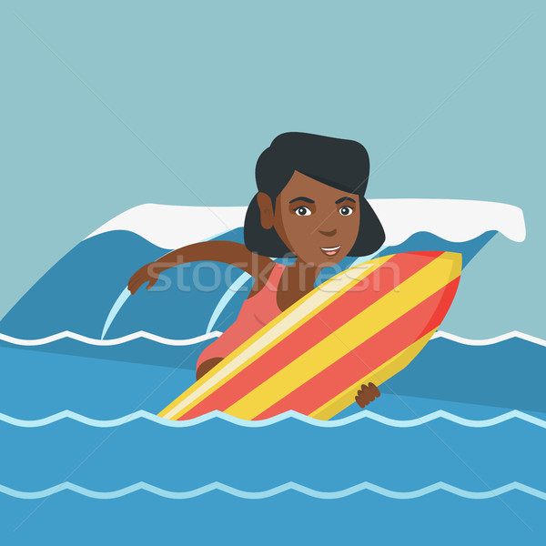 Stock photo: Young african-american surfer on a surfboard.