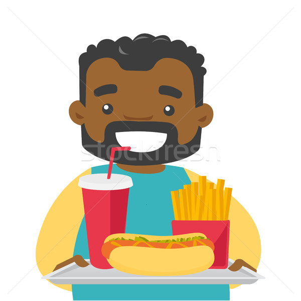 Young african man holding tray full of fast food. Stock photo © RAStudio