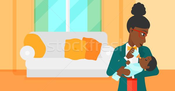 Stock photo: Woman feeding baby.