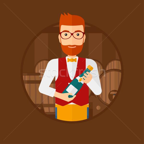 Waiter holding bottle in wine cellar. Stock photo © RAStudio