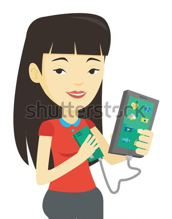 Woman reharging smartphone from portable battery. Stock photo © RAStudio
