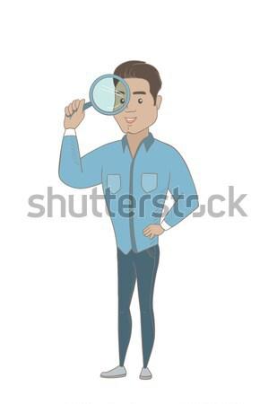 Young hispanic businessman with magnifying glass. Stock photo © RAStudio