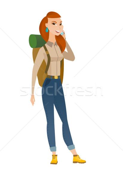 Traveler woman talking on a mobile phone. Stock photo © RAStudio