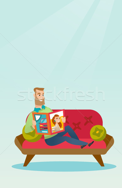 Stock photo: Man reading a magazine on the couch.