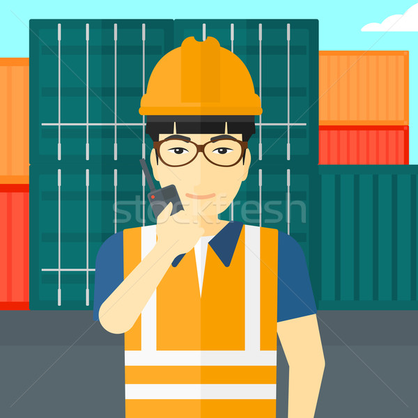 Stevedore standing on cargo containers background. Stock photo © RAStudio