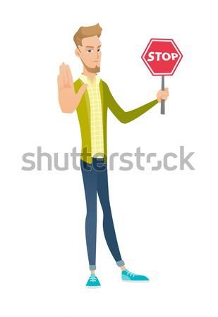 Caucasian traveler holding stop road sign. Stock photo © RAStudio