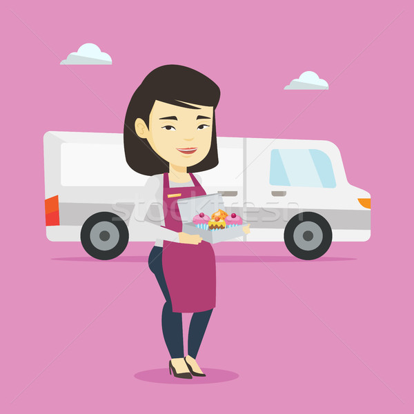Delivery woman holding a box of cakes. Stock photo © RAStudio